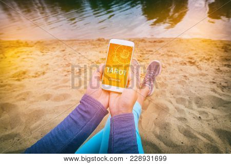 Woman holding smartphone with modern fortunetelling application on screen. Divination addiction concept