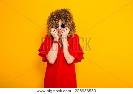 Portrait Of A White Scared Woman With Afrro Curly Hairstyle In Red Dress And Sunglasses Holds Hands