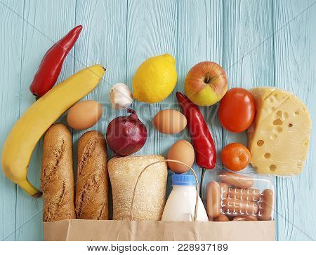 Paper Bag With Different Useful Food, Vegetables And Fruits On Blue Wooden