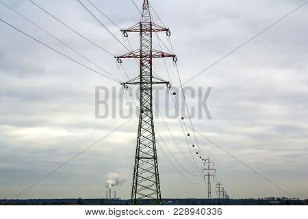 Pylons And Power Lines With Vibrant Sky, Clouds And Sun. High Voltage Electric Towers. Transmission