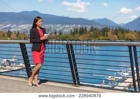 Vancouver city Asian canadian woman drinking coffee at harbor view during office break in the morning. Professional businesswoman thinking outside in the sun.