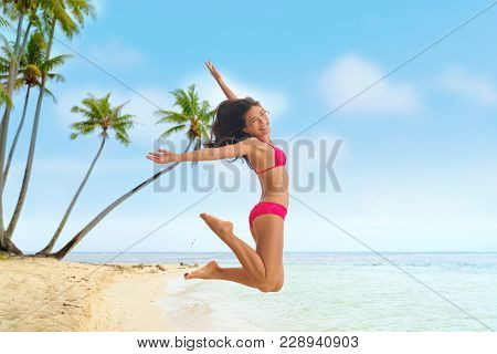 Beach fun summer vacation under the sun joyful happy bikini woman jumping of joy on Tahiti luxury travel destination. Asian girl happiness jump.