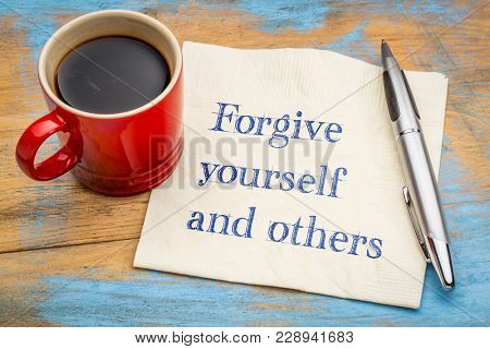 Forgive yourself and others advice - handwriting on a napkin with a cup of coffee