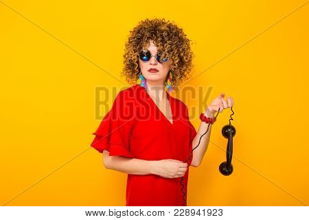 Portrait Of A White Displeased Woman With Afrro Curly Hairstyle In Red Dress And Sunglasses Holding