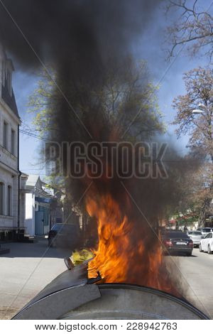 Red Blaze And Black Smoke. The Fire Into A Dustbin On The Street.
