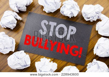 Hand writing text caption showing Stop Bullying. Business concept for Prevention Problem Bully written on sticky note paper the wooden background with folded paper meaning thinking poster