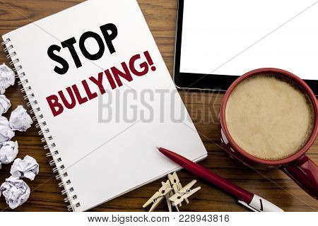 Conceptual hand writing text caption inspiration showing Stop Bullying. Business concept for Prevention Problem Bully written on notepad paper on the wood table with coffee in office poster