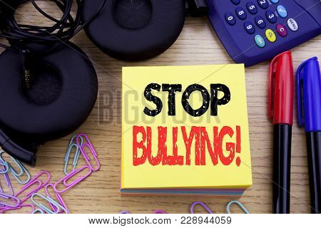 Word, writing Stop Bullying. Business concept for Prevention Problem Bully written on sticky note paper on wooden background. With calculator and pen marker and headphones poster