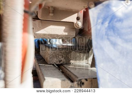 View Through An Angle Grinder Of The Circular Saw Blade Cutting A Paving Stone And The Hands Of A Wo