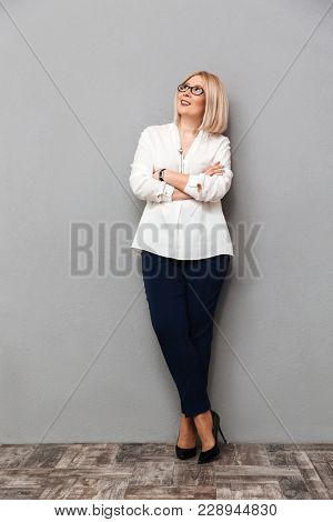 Full length image of Smiling middle-aged blonde woman in elegant clothes and eyeglasses posing with crossed arms and looking up over grey background