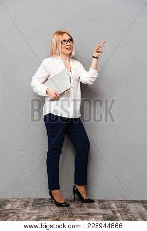 Full length image of middle-aged blonde woman in elegant clothes and eyeglasses holding laptop computer while pointing on copyspace and looking away over grey background