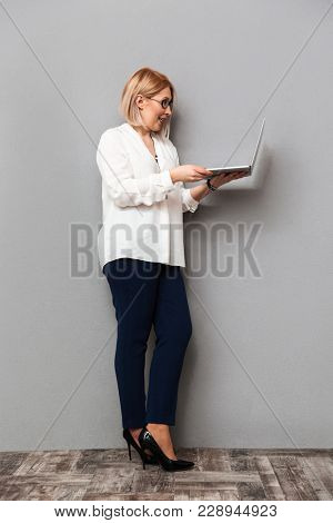 Full length image of happy middle-aged blonde woman in elegant clothes and eyeglasses posing sideways while using laptop computer over grey background
