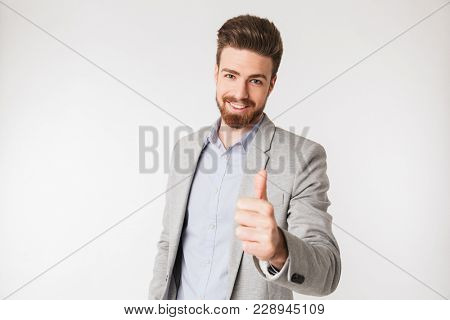 Portrait of a smiling young man dressed in shirt and jacket showing thumbs up isolated over white background