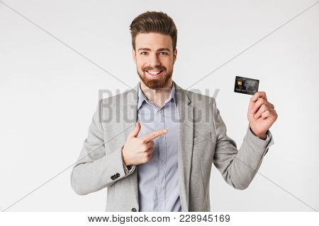 Portrait of a smiling young man dressed in shirt and jacket pointing finger at a credit card isolated over white background