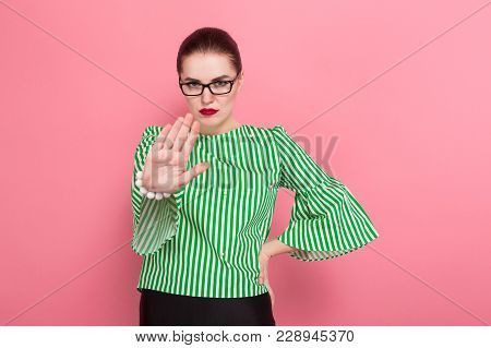 Portrait Of Attractive Cheerful Businesswoman With Hair Bun In Striped Blouse And Eyeglasses Showing