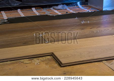 Renovation Works. Close-up Of Installation Of Parquet And Ceramic Tile Floor And Heating Cables For