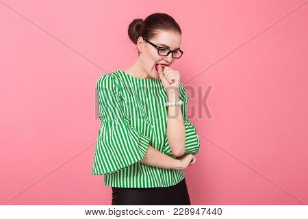 Portrait Of Attractive Scared Businesswoman With Hair Bun In Striped Blouse And Eyeglasses Biting He