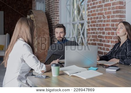 Group Of Professional Web Designers Working Together In Co-working Space, Using Portable Laptop Comp