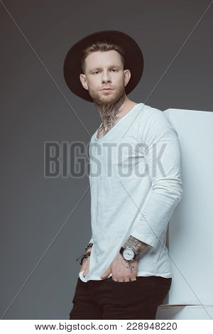 Stylish Young Tattooed Man In Black Hat Standing With Hands In Pockets And Looking At Camera Isolate
