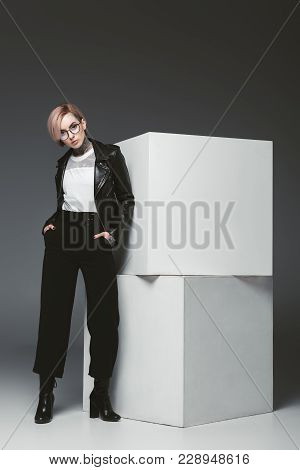 Fashionable Young Woman In Leather Jacket And Eyeglasses Standing With Hands In Pockets And Looking