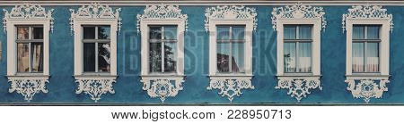 Row of historic windows with ornate intricate white stucco surrounds or moldings on a blue wall in a panoramic banner from a landmark house in Bamberg, Bavaria