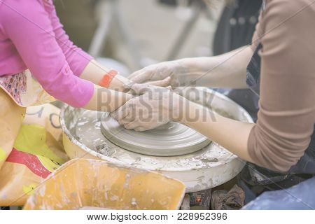 Female Hands Of Potter And Girl S Hands . Master Teaches Student To Make Pitcher On Pottery Wheel. M