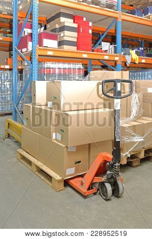 Pallet With Boxes At Pump Jack Truck In Warehouse