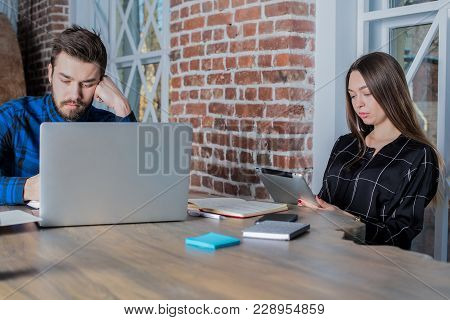 Man And Woman Marketers Having Hard Long Work Day In Office, Using Laptop Computer And Touch Pad. Tw