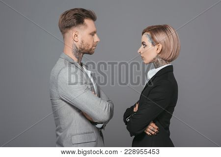 Stylish Businessman And Businesswoman With Crossed Arms Looking At Each Other, Isolated On Grey