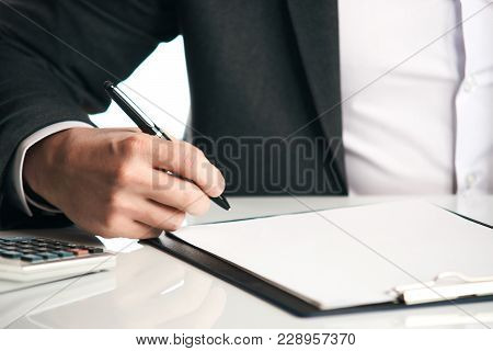 Close Up Of Human Hand Signing A Document. Businessman Works With Papers In His Office. The Agreemen