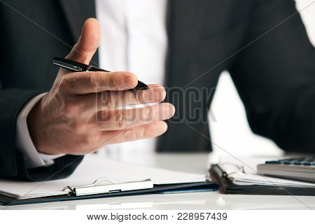 Businessman sitting at the table and explaining something, close-up. Sales Clerk insurer talking trying to convince to client at desk in office over white background poster