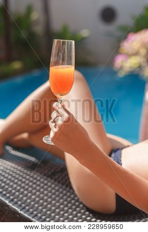 Cropped Shot Of Woman In Bikini Lying In Sun Lounge At Poolside
