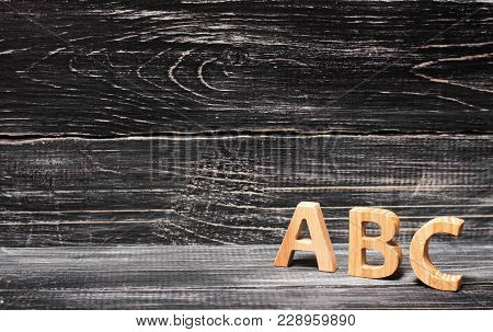 Alphabet made of wood on the background of a board, ebony. Concept of education, English. English letters, retro. poster