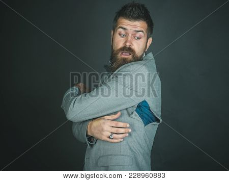 Man With Beard Wears Jacket With Hole On Dark Background. Hipster Chose Small Size Jacket, Seam Torn