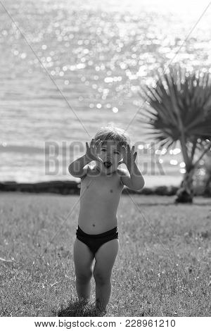 Cute Cheerful Baby Boy With Blond Hair In Red Trunks Makes Frightening Attacking Gesture Outdoors On