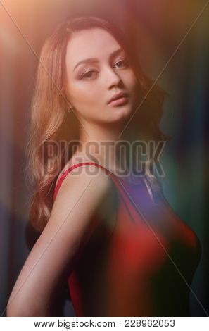 Charming brunette in a red dress posing on a black background.