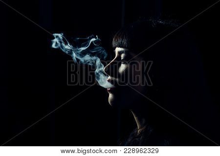 Womans Head With Smoke In Mouth On Black Background. Side View And Shape Of Female Face And Smoke. S