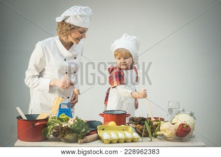 Mother Teaches Son To Cook On Light Background. Parents Little Helper Concept. Chef And Assistant Ne