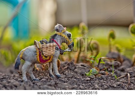 A Donkey In A Clearing Of Green Grass. A Loaded Toy Donkey On A Green Background. Copy Space
