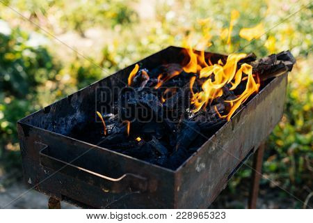 Coals Burn In The Grill On The Background Of Nature