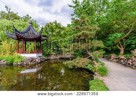 A Path Near A Pond With A Wooden Bridge And A Pavilion Reflected In It In A Chinese Garden With Tree