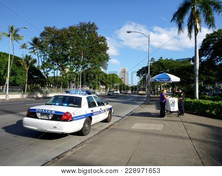 Honolulu - February 2, 2012:  Honolulu Police Department Police Officer Tickets Woman Running A Ice