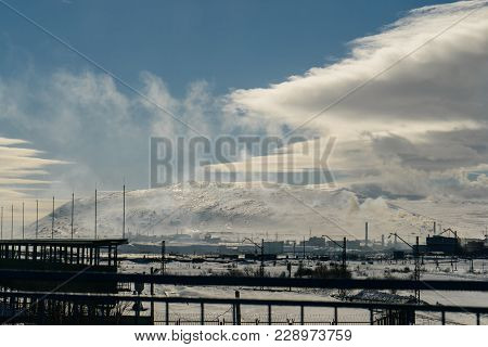 Snow-capped City Against The Backdrop Of High Mountains