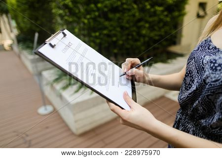 Large Hand Portrait Of Subscribers Sign Contract On Background Of New Building With Swimming Pool. C