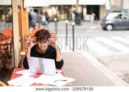 aged female screenwriter sitting in outdoor cafe and reproduce scenario from paper drafts in text file on laptop. Lady dressed in black cardigan looks like very pleased with work. Woman scans pages and removes lying glasses aside. Concept of importance of poster