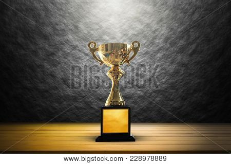 Champion Golden Trophy On Wooden Table Background. Copy Space.