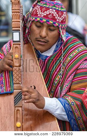Otavalo, Ecuador - February 17, 2018: Peruvian Indigenous Musician In Traditional Clothing Performin