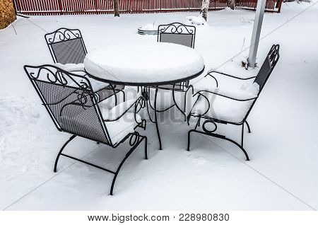 Black Patio Furniture And A Fire Pit Covered In Snow On A Winter Day