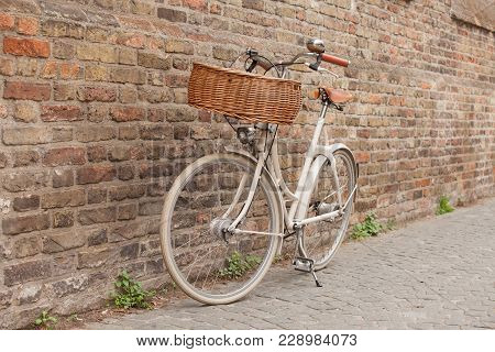 White Bike With Basket Standing Near Brick Wall In Brugge, Belgium