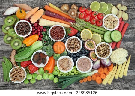 Healthy super food sampler with fresh vegetables, fruit and herbal medicine, in porcelain dishes and loose, top view on rustic background. Health food concept high in antioxidants & anthocyanins.